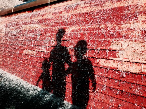While checking out a sidewalk chalk exhibition at Crown Center in Kansas City, the shadows of my three children fell across the fountain wall, and I quickly snapped a photograph of their silhouettes.